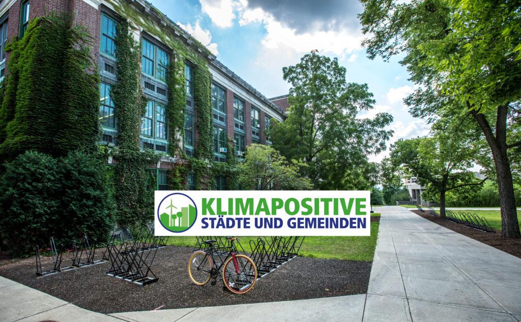 Klimaschutz - bewachsenes Gebäude mit Fahrradständer von Bäumen umgeben